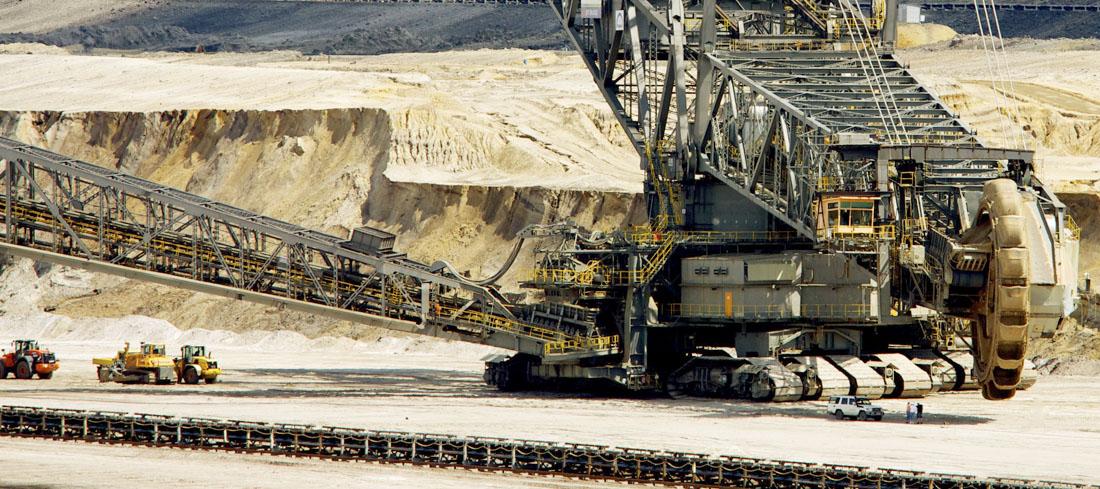 Ein Teil eines Kohlbaggers in einem Tagebau ist zusehen. Kleinere Fahrzeuge stehen neben dem großen Bagger.