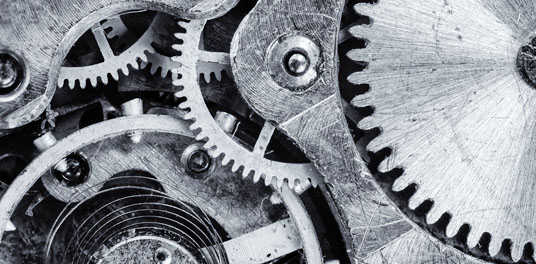 Mehrere mit einander verbundene, metallische Zahnräder bilden eine Art Uhrwerk.